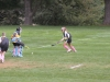 Junior Bethany Boniface (left) and senior Ally Kozel (right) charge the goalie, sophomore Eleanor Cohan (center).  The varsity field hockey team sport their pink socks and ribbons in support of the Band Aid Drive.