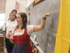 German teacher, Ashleigh Stall teaches a German song to her class during Oktoberfest, as music teacher Marc Bolden and junior Matthew Wagner wacth intently.